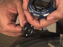 Using a stopwatch to time how long a wheel will spin with different nail finishes.